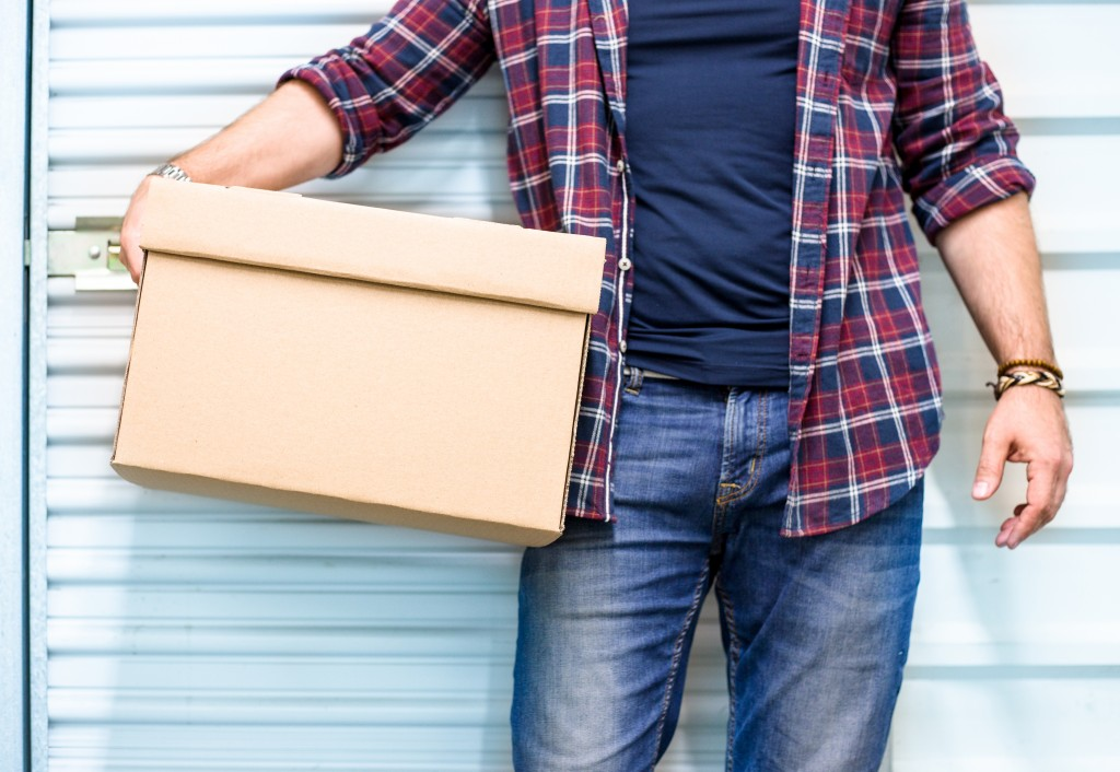 man holding a box in a garage background