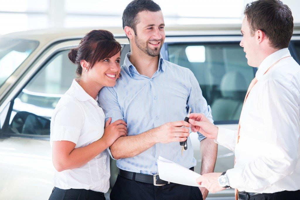 Smiling couple buying a new car from a salesman