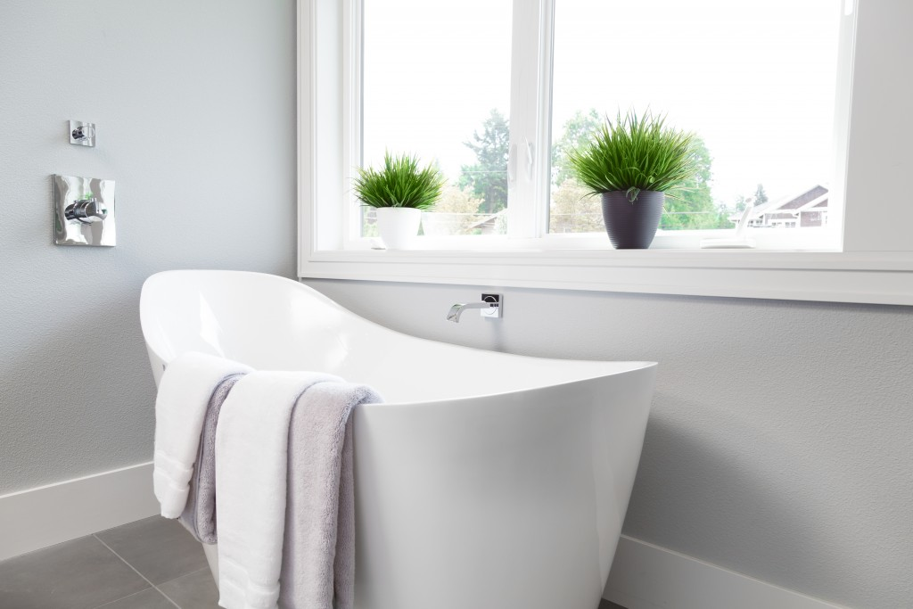 bathroom with white bathtub, towels, and plants