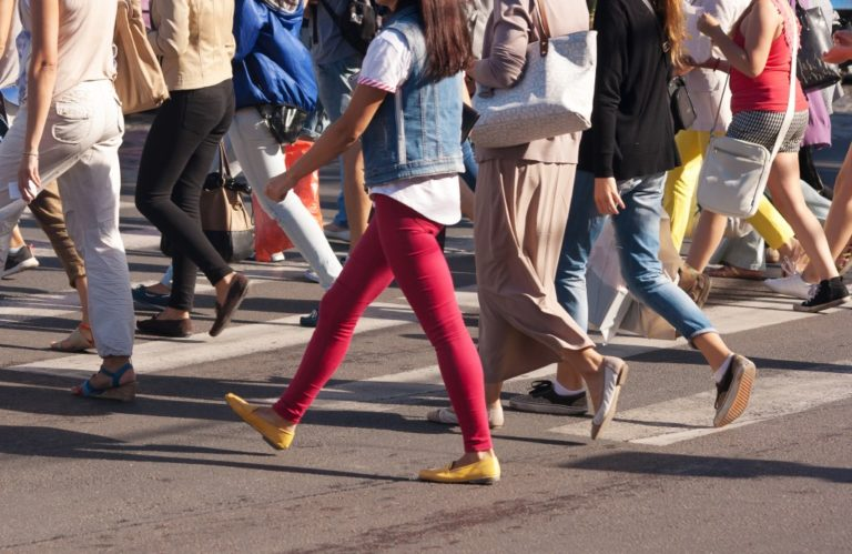 feet of young pedestrians walking on the crosswalk on summer day