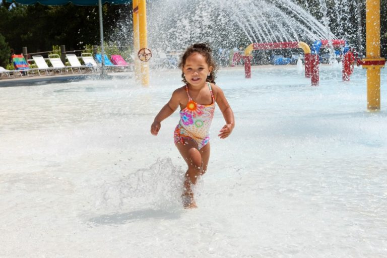 Little girl running in the waterpark