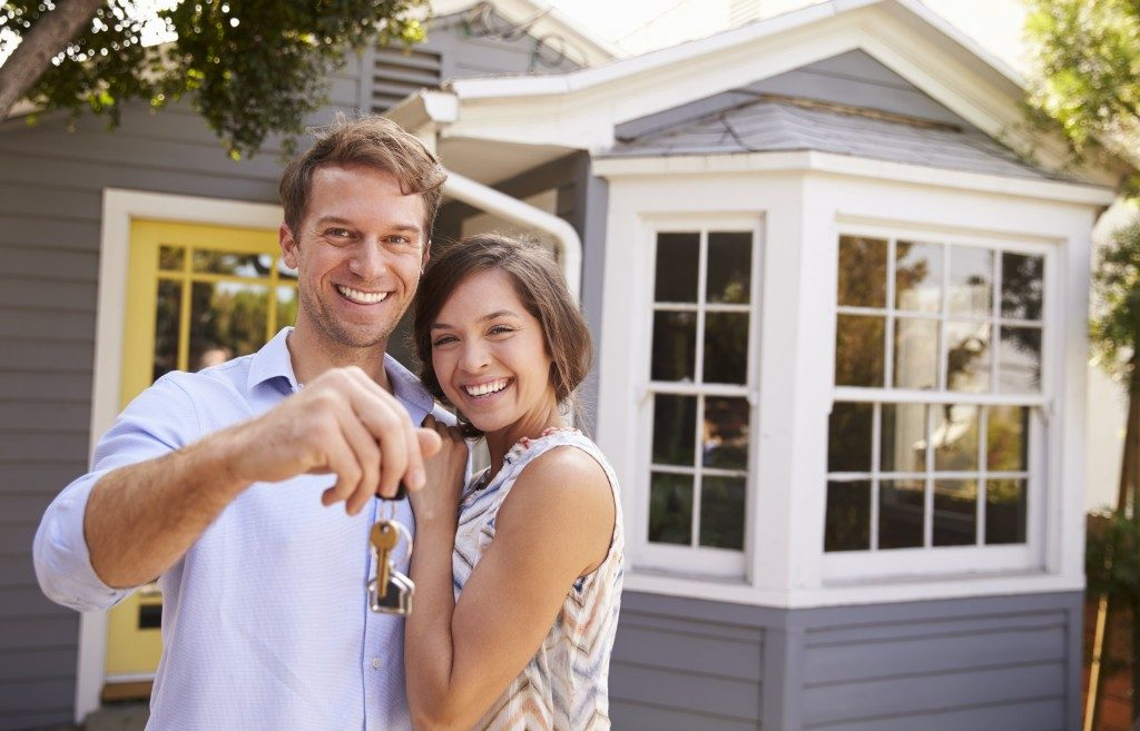 couple happy holding keys to new home